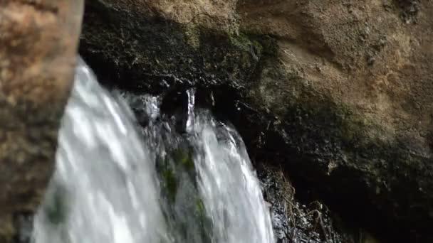 depositphotos_189061620-stock-video-spring-water-flowing-rock-stones